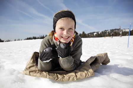 untruth: portrait of a girl lying down in the snow Stock Photo