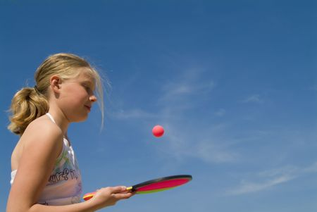 girl playing a ball game at the beach (blue sky)