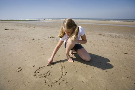 puppy love: puppy love, girl drawing a heart in the sand at the beach