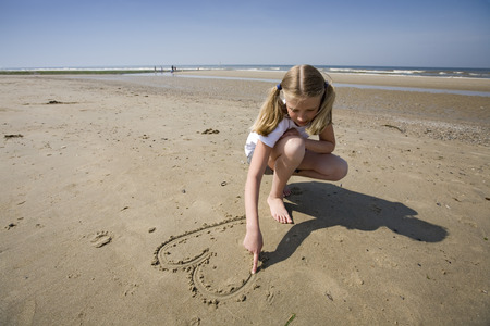 puppy love, girl drawing a heart in the sand at the beach