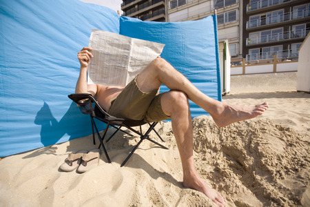 man reading his paper at the beach photo