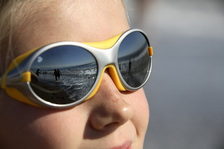 girl with sunglasses (reflecting the beach)