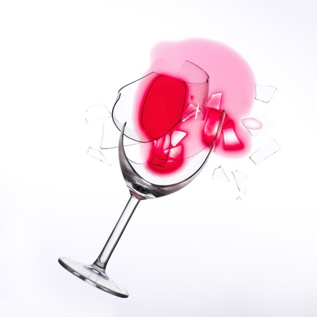 fallen wine glass with red wine in it and red stain on a white tablecloth Stock Photo
