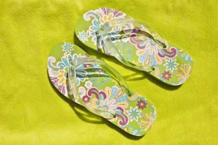 feat: verde brillante flip-flops en un �rea verde toalla de playa