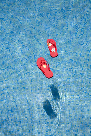 red flip-flops floating in a swimmingpool