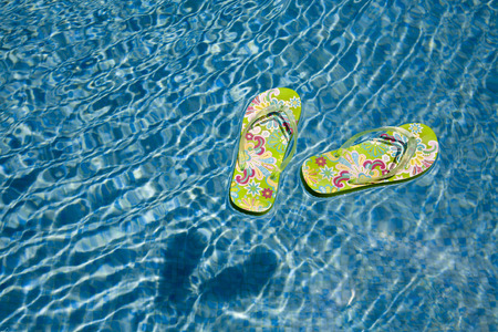 green flip flops floating in the swimming pool
