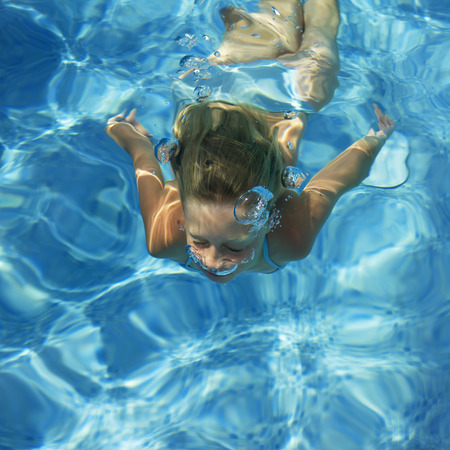 girl swimmin under water in a swimming pool, breathing out with air bubbles Stock Photo