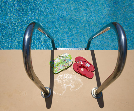 swimmingpool: top view at a swimmingpool with blue mosaic tiles, steps and flip flops.