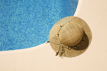 summer hat at the side of a swimming pool