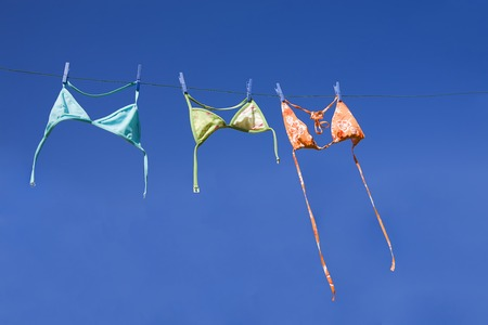 Three colorful bikini tops drying on washing line (blie sky, summer vacation concept) Stock Photo