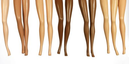 legs from plastic dolls with different colors of skin Stock Photo