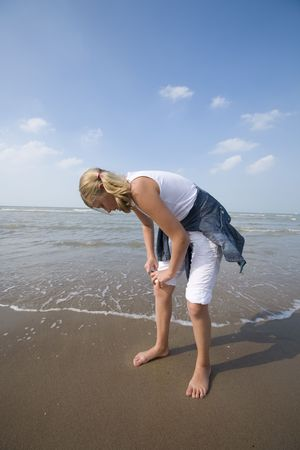 girl rolling up her pants for a walk along the beach photo