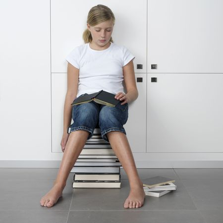 annoyed girl: teenage girl who fell asleep over her books, while sitting on a stack of books Stock Photo