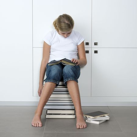 teenage girl who fell asleep over her books, while sitting on a stack of books Stock Photo