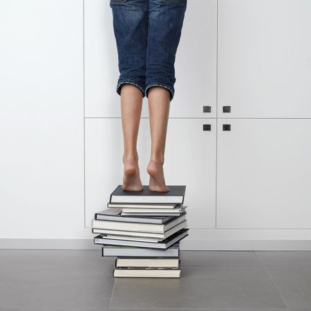 teenage girl standing on top of a stack of books, trying to reach one in the library