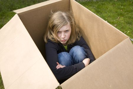 angry teenage girl sitting in a cardboard box, looking up Stock Photo