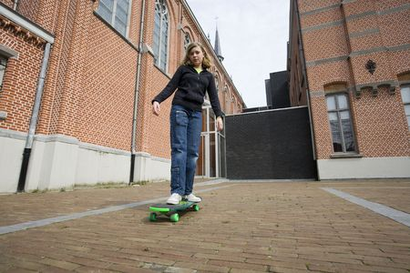 bore: girl standing on her skate board (looking bored) Stock Photo