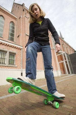 teenage girl standing on her skate board (looking surprised) photo