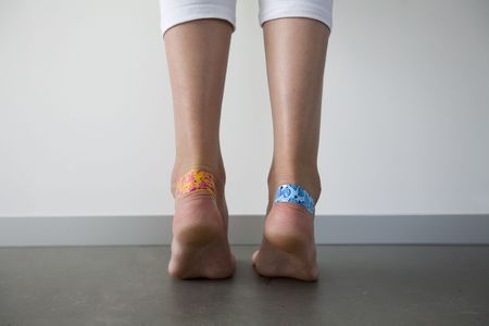 plaster foot: girl with colorful adhesive plasters on the blisters on her heels