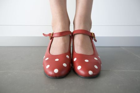 close-up of feet in red shoes with white dots
