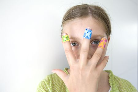 girl with coloful adhesive plasters on her fingers (focus on eyes) photo