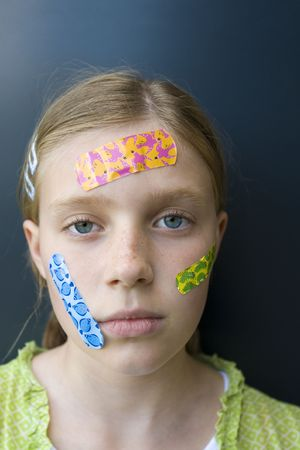 firstaid: portrait of a girl with several colorful bandages on her face, looking sad
