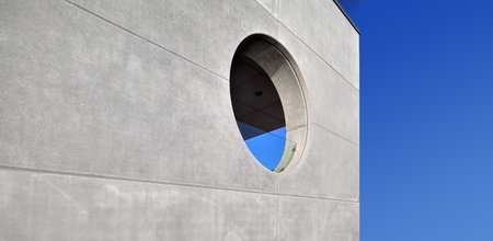 concrete building, round window, blue sky