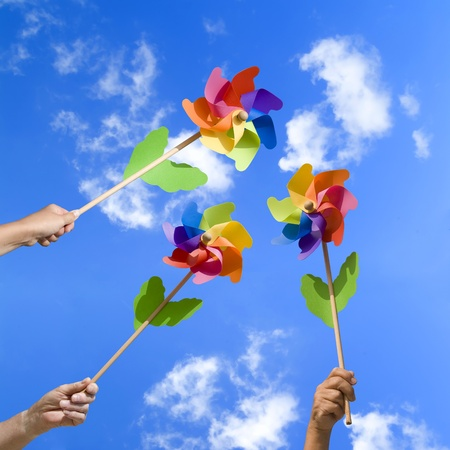 people with colorful small windmills in their hands, blue sky photo