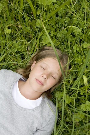 young girl (blue eyes, blonde) lying in the grass dreaming of ... photo