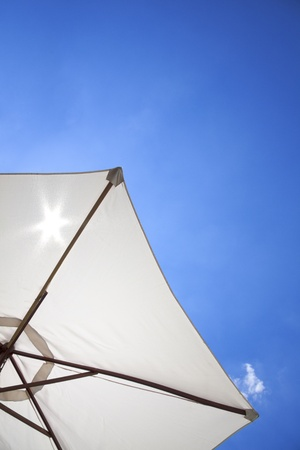 white linen umbrella in front of a deep blue sky Stock Photo