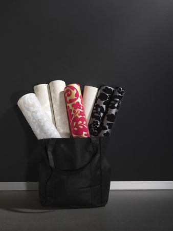 luxury wall paper rolls arranged in a black basket, copy space