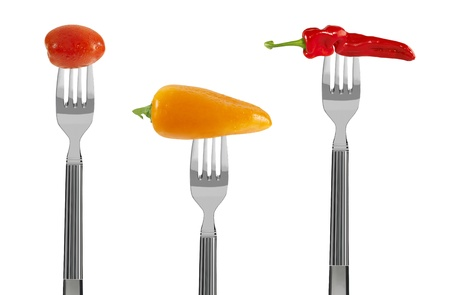freshh red and yellow baby vegetables on forks, isolated on white