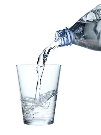 pouring mineral water in a water glass, isolated on white