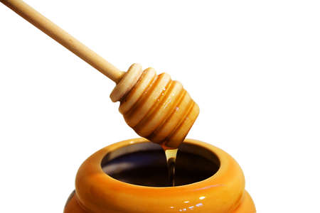 wooden honey drizzler with a stream of honey showing top of jar.