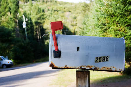 Old mailbox on a rural road with the flag up