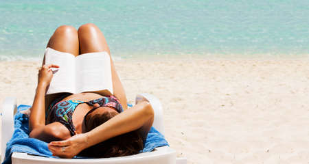 Pretty girl reading novel at beautiful beach Reklamní fotografie