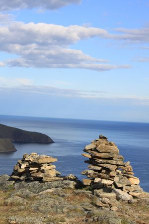 view from top of the mountain on the lake Baikal. Conglomeration of stones made by shaman. photo
