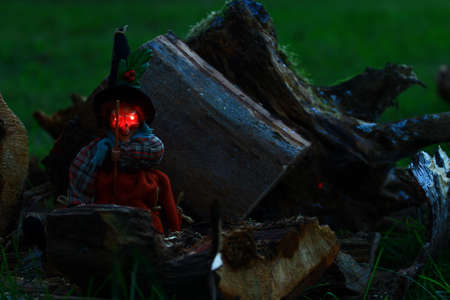 A witch with red eyes sitting on a piece of sawn wood