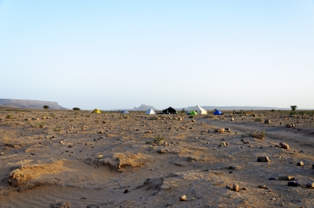 Hamada du Draa  Morocco stone desert , stones and sand in foreground and tents in background photo