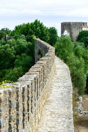 bulwark: Old bulwark and castle in background, Obidos  Portugal