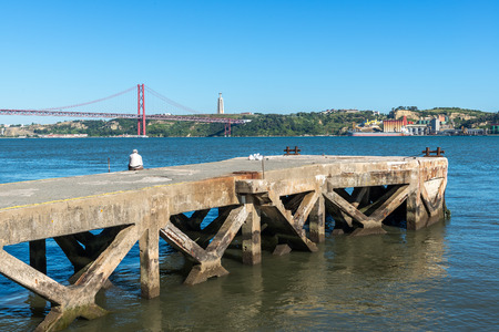tagus: Fisher on a pier at Tagus river with bridge in background, Lisbon  Portugal  Stock Photo