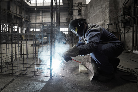 Welder with protective mask welding reinforcement bars Stock Photo