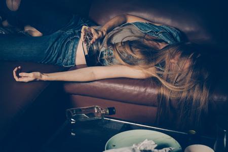 Joven borracha en el sofá. Joven borracha en el sofá. El alcoholismo y la adicción a las drogas conducen a la depresión. Foto de archivo