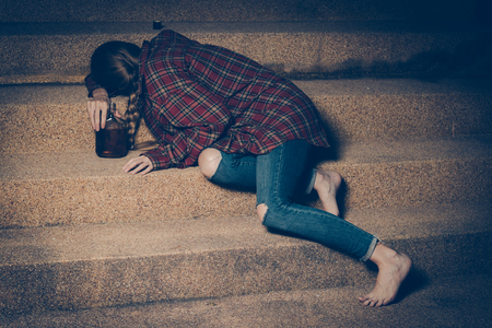 Young drunk woman sitting outside in night. Alcoholism and drug addiction lead to depression.