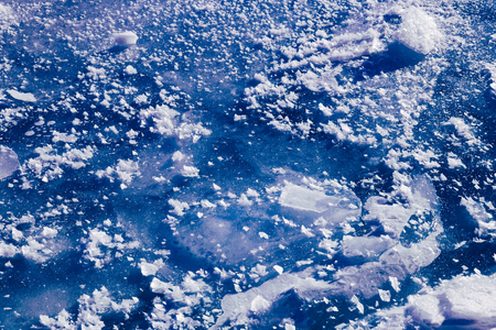 Blue ice texture. Abstract arctic winter background. Winter ice along the shore.