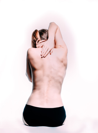 Beautiful athletic blond caucasian woman's body. Nude woman back. Naked woman in towel is sitting. Studio shot Back view, isolated on white background. Standard-Bild - 119366570