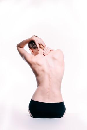 Il corpo della bella donna caucasica bionda atletica. Donna nuda indietro. La donna nuda in asciugamano è seduta. Studio girato Vista posteriore, isolata su sfondo bianco.