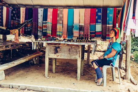 Long Neck Woman weave cloth in front her house in tribal village Northern Thailand. Stock Photo