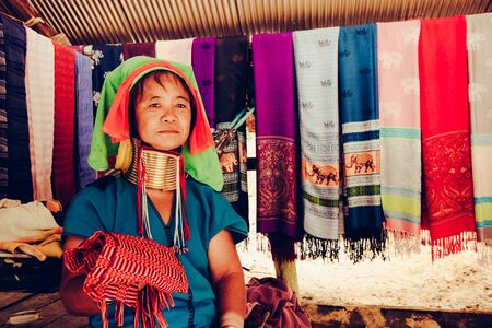 Long Neck Woman weave cloth in front her house in tribal village Northern Thailand.