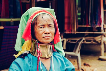 Portrait of Long Neck Woman weave cloth in front her house in tribal village Northern Thailand.